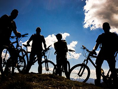 The silhouettes of four people outside on their mountain bikes
