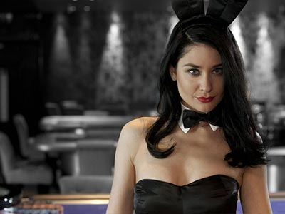 A girl dressed in bunny ears and a bow tie, in a casino