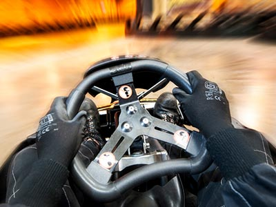 A person's hands on the steering wheel of a go kart, with the background blurred