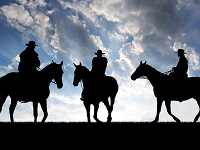 Silhouette of three people sat on horses, to a backdrop of the sky
