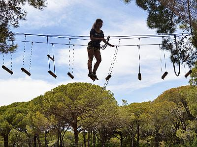 A woman crossing a rope bridge in the air to a backdrop of trees