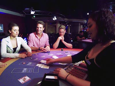 A girl croupier dealing cards out to some people in a casino