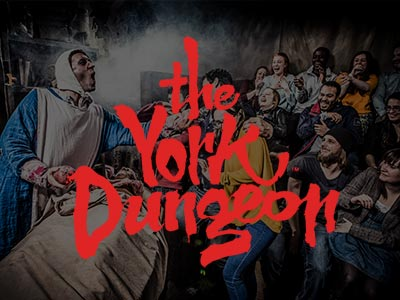 The York Dungeon logo written over actors in the dungeon performing to the crowd