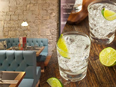 A split image of some seats in Revolution and some glasses of drink with lime and ice in