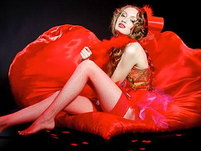 Close up of a woman reclining back on a red beanbag in a red burlesque outfit, whilst wearing a red trilby