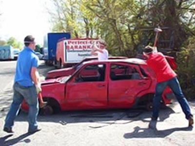 Two men smashing up a car