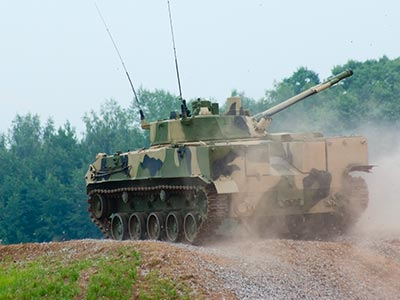 A tank driving over rough terrain