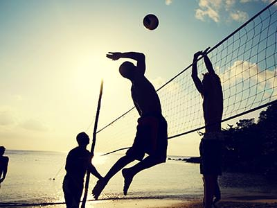 Close up silhouette of two men reaching up to hit a volleyball, with a volleyball net between them and others looking on in the background, to a sunset backdrop