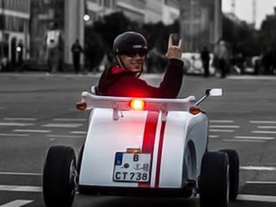 A man doing the rocker sign in a little car