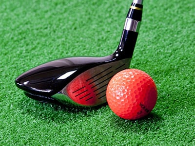 A golf club addressing a ball on a tee