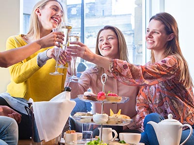 Three girls having afternoon tea and toasting their glasses together over it