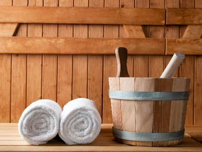 Two towels rolled up with a bucket in a wooden building