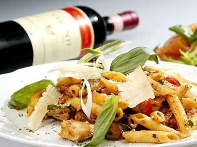 A plate of pasta with a bottle of red wine to the side