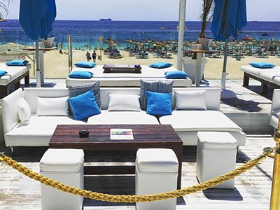 A white booth in Ocean Beach Club with the sea and beach in the background