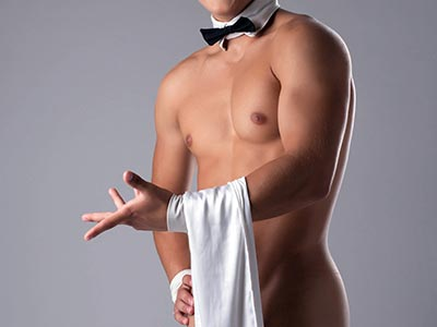 A man wearing just a bow tie and cuffs, holding a white towel which covers his penis