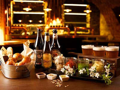 A banquet set up on a wooden table of beers and bread