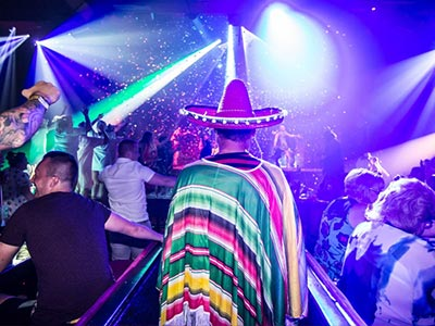 A man wearing a sombrero and Mexican outfit in a club