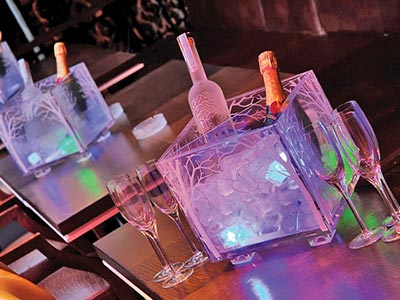 Illuminated boxes of alcohol on tables