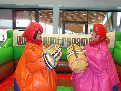 Two girls playing the Vicky Pollard Handbags game at West Country Games