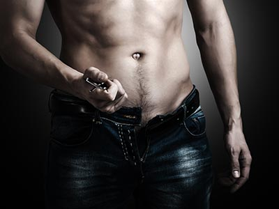 A close up of a topless man unbuckling his jeans