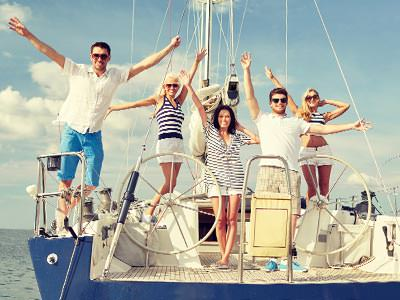 Close up of men and women posing on the deck of a boat