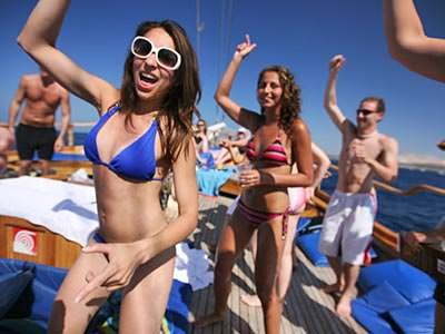 A group of people in swimwear dancing on the deck of a boat