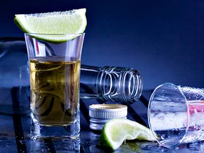 A shot of tequila with a lime on top, and an empty bottle and shot glass on their sides in the background