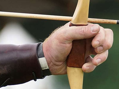 A man's hand on a bow and arrow