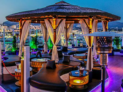 Leather seating underneath a canopy with curtains on the rooftop terrace at Pangea, with buildings in the background