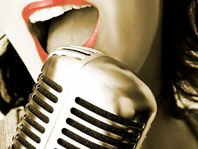Close up of a woman's mouth singing into an old-style mic