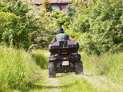 A man on a quad bike driving into the distance