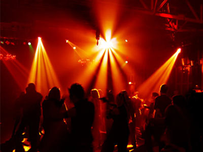 People dancing in a nightclub with red and yellow lights