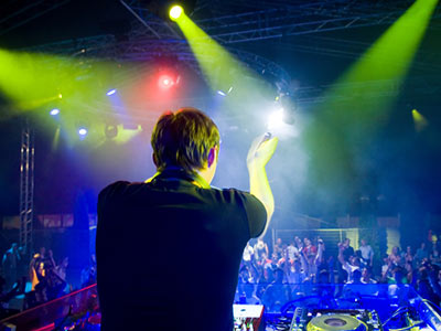 A dj with a crowd in the background, in a nightclub