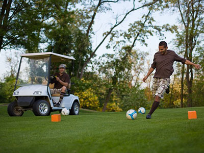 A person kicking a football on golf course