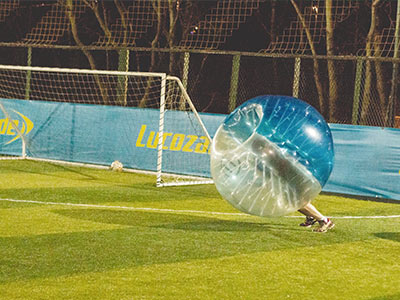 A person in an inflatable football, on a pitch