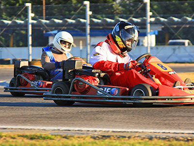 Two people in go-karts, outdoors