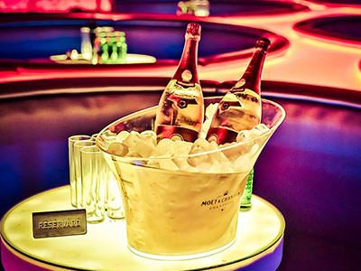 Two bottles of champagne in an ice bucket on top of a table, with leather booths in the background