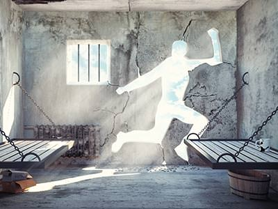 A stone prison cell with the outline of a person cut out of the wall