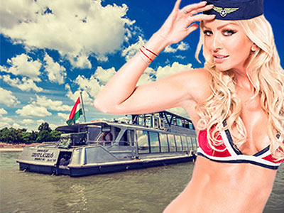 Close up of a woman in a pilot hat and bra, saluting against a background of a boat on a river