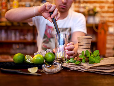 A man making a cocktail behind a bar