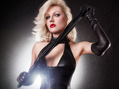 A woman in black leather, holding a whip