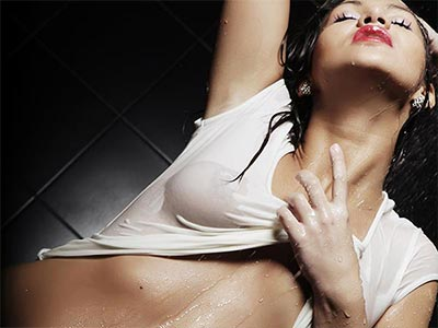 A woman pulling up her wet, white top