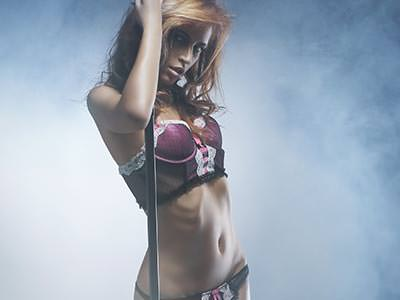 Close up of a woman holding onto a pole whilst wearing a pink bra and knickers, to a smoky backdrop