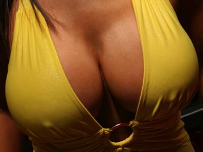 Close up of a massive pair of breasts in a banana yellow swimming suit, with nipples visible through the costume