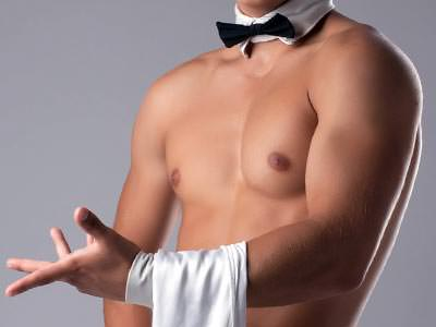 A naked male torso in a black and white bowtie, holding a white towel on his wrist to a grey backdrop