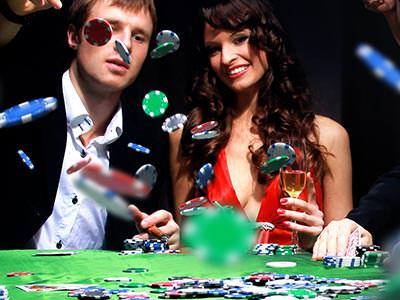 Close up of a man throwing poker chips on a table whilst sat next to a woman