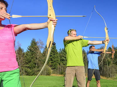 A group of people outside on a sunny day, aiming with a bow and arrow