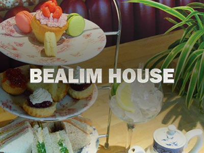A selection of sandwiches and cakes on a stand, with a drink next to it and the Bealim House logo overlapping