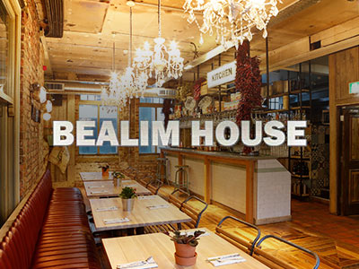A dining area with a bar in the background and the Bealim House logo overlapping