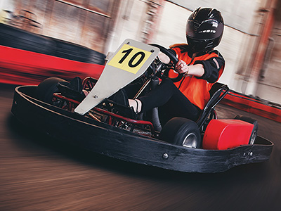A person in a red go kart speeding around a track